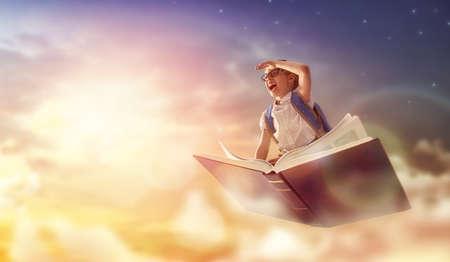 Zurück zur Schule! Glückliches nettes arbeitsames Kinderfliegen auf dem Buch auf Hintergrund des Sonnenunterganghimmels. Konzept der Erziehung und des Lesens. Die Entwicklung der Vorstellungskraft. Standard-Bild