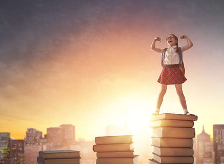 Back to school! Happy cute industrious child standing on books on background of sunset urban landscape. Concept of education and reading. The development of the imagination. Stock Photo - 81604271