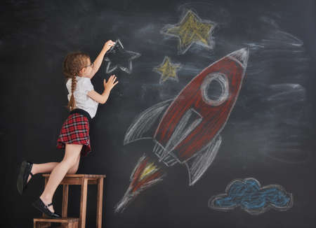 Back to school! Happy cute industrious child is drawing stars and rocket on blackboard. Kid is learning in class.