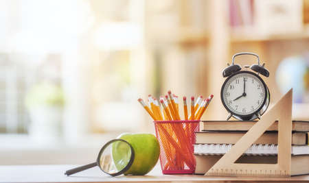 Back to school and happy time! Apple, pile of books and pencils on the desk at the elementary school.  Zdjęcie Seryjne