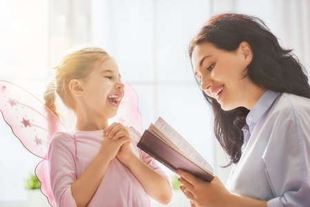resting: Pretty young mother reading a book to her daughter. Family holiday and togetherness. Stock Photo
