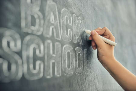 Back to school! Happy cute industrious child is writing on blackboard. Kid is learning in class. Close up.