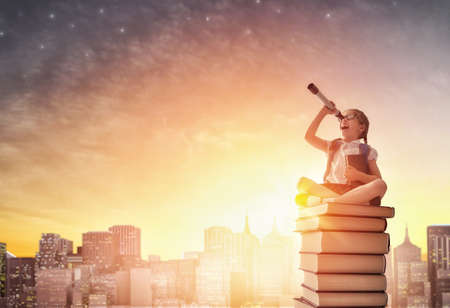 Back to school! Happy cute industrious child standing on books on background of sunset urban landscape. Concept of education and reading. The development of the imagination.