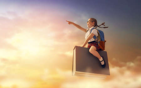 Back to school! Happy cute industrious child flying on the book on background of sunset sky. Concept of education and reading. The development of the imagination. Stock Photo