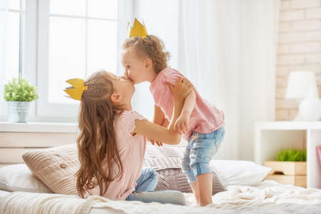 bedroom: two cute children baby girls playing and having fun in the kids room. loving sisters with crowns on the bed.
