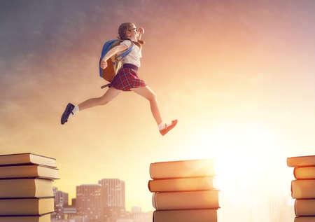 ¡De vuelta a la escuela! Niño trabajador lindo feliz corriendo y saltando en los libros en el fondo del paisaje urbano de la puesta del sol. Concepto de educación y lectura. El desarrollo de la imaginación. Foto de archivo