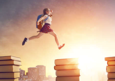 Back to school! Happy cute industrious child running and jumping on books on background of sunset urban landscape. Concept of education and reading. The development of the imagination. Stock Photo
