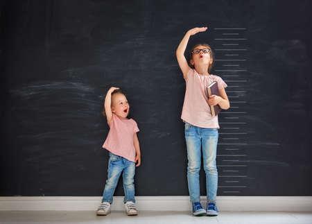 Dos hermanas de niños juegan juntos. Niño mide el crecimiento en el fondo de la pizarra. Concepto de educación. Foto de archivo - 82359642