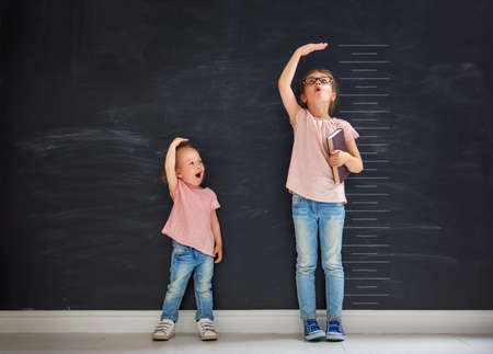 Two children sisters play together. Kid measures the growth on the background of blackboard. Concept of education. Imagens - 82359642