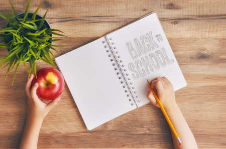 Regreso a la escuela y tiempo feliz! Escritorio de madera. Un niño escribe en un cuaderno vacío. Vista superior. Foto de archivo - 82359678