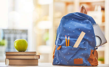 Back to school and happy time! Apple, pile of books and backpack on the desk at the elementary school. Standard-Bild