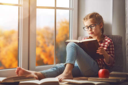 Cute child girl sitting by the window and reading a book in room at home. Beautiful autumn nature. Banque d'images