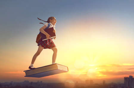 Back to school! Happy cute industrious child flying on the book on background of sunset urban landscape. Concept of education and reading. The development of the imagination. Stok Fotoğraf - 82359851