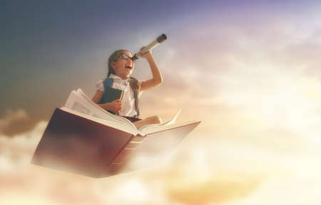 Back to school! Happy cute industrious child flying on the book on background of sunset sky. Concept of education and reading. The development of the imagination. Standard-Bild