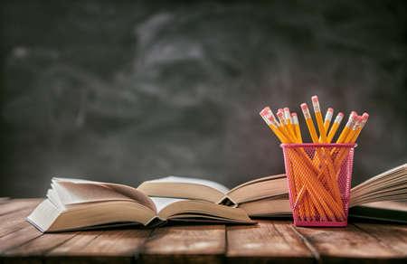 学校との幸せな時間!鉛筆と黒板の背景に机の上の本の山。