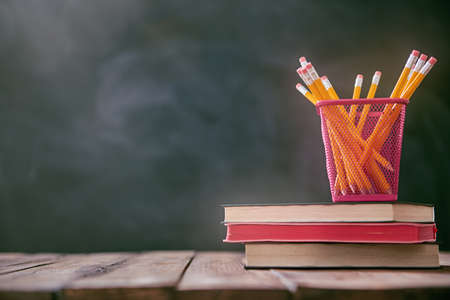 Back to school and happy time! Pencils and pile of books on the desk on background of blackboard.