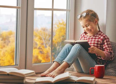 窓のそばに座って、自宅の部屋で本を読んでは女の子をかわいい子。秋の美しい自然。 写真素材 - 82856300