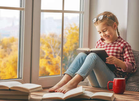 Cute child girl sitting by the window and reading a book in room at home. Beautiful autumn nature. Stockfoto