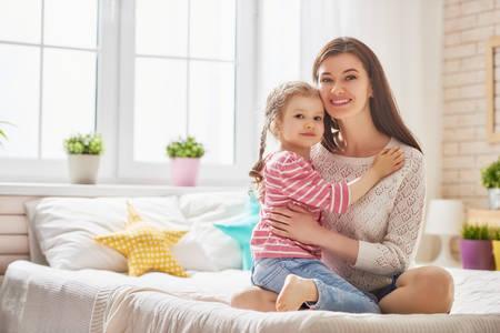 Mama en haar dochterkindmeisje spelen, glimlachen en knuffelen. Gezinsvakantie en samenhorigheid.