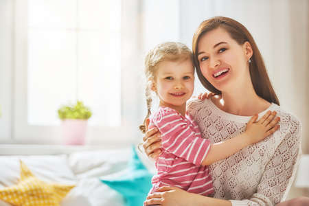 Mom and her daughter child girl are playing, smiling and hugging. Family holiday and togetherness.