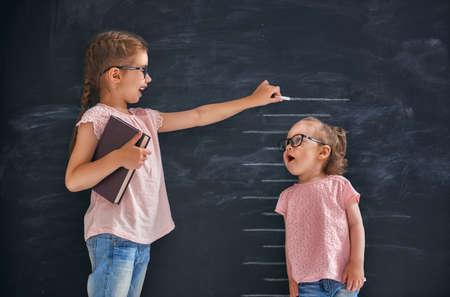 Due sorelle figli giocano insieme. Il bambino misura la crescita sullo sfondo della lavagna. Concetto di educazione.