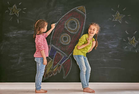 Back to school! Two happy cute industrious children are drawing stars and rocket on blackboard. Kids are learning in class. Imagens