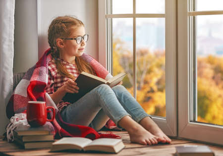 Cute child girl sitting by the window and reading a book in room at home. Beautiful autumn nature. Stok Fotoğraf