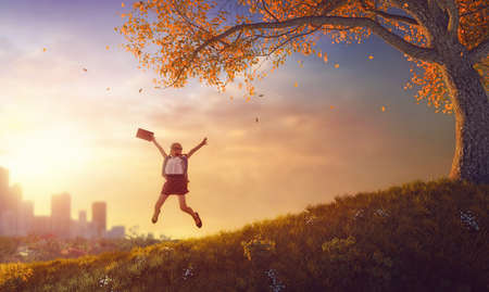 Back to school! Happy cute industrious child jumping with book near tree on a sunset urban landscape. Concept of successful education and reading. Stock Photo