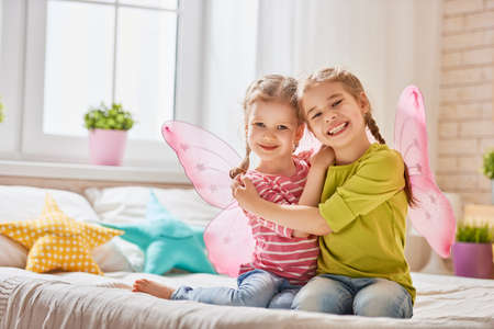 Two cute children baby girls playing and having fun in the kids room. Loving sisters with wings on the bed.