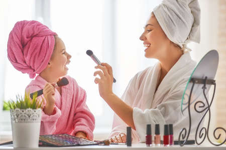 Happy loving family. Mother and daughter are doing make up and having fun sitting at dressing table at home. Mom and child girl are in bathrobes and with towels on their heads. Imagens
