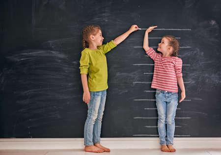 Irmãs de duas crianças brincam juntos. Garoto mede o crescimento no fundo do quadro-negro. Conceito de educação. Foto de archivo - 83258635