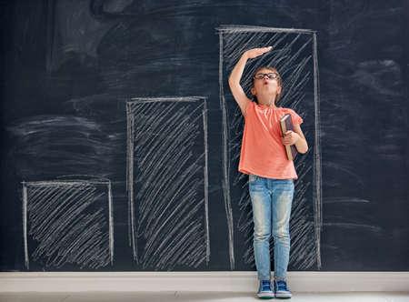 かわいい子は遊んでいます。子供は、黒板の背景に成長を測定します。教育の概念。 写真素材