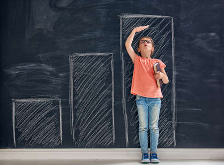 Cute child is playing. Kid measures the growth on the background of blackboard. Concept of education.