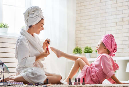 Happy loving family. Mother and daughter are doing manicures, pedicure, make up and having fun. Mom and child girl are in bathrobes and with towels on their heads.