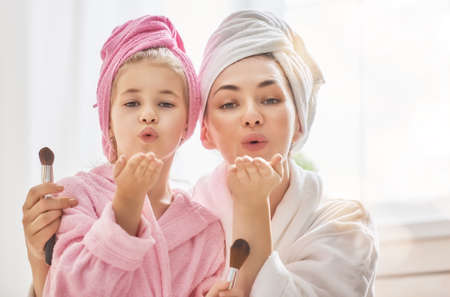 Happy loving family. Mother and daughter are having fun. Mom and child girl are in bathrobes and with towels on their heads. Stock Photo