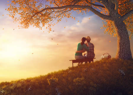 Happy couple in love. Stunning sensual portrait of young stylish fashion couple picnicking together near a tree in autumn park. Archivio Fotografico