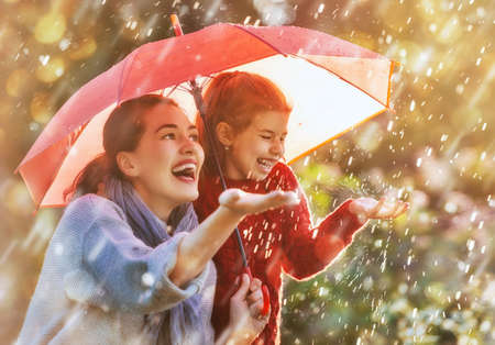 Happy funny family with red umbrella under the autumn shower. Girl and her mother are enjoying rainfall. Kid and mom are playing on the nature outdoors. Walk in the park. Banco de Imagens - 83441398