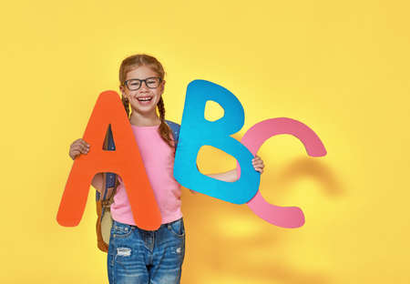 Back to school! Happy cute industrious child with big letters indoors. Kid on color background. Yellow, blue and pink.