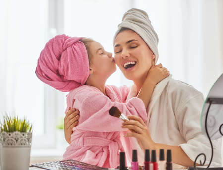 Happy loving family. Mother and daughter are doing make up and having fun sitting at dressing table at home. Mom and child girl are in bathrobes and with towels on their heads. Stock Photo