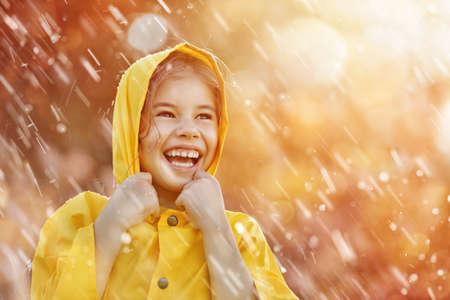 Niño divertido feliz bajo la ducha de otoño. Chica está usando impermeable amarillo y disfrutando de la lluvia.