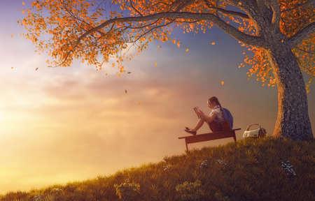 ¡De vuelta a la escuela! Niño trabajador lindo feliz leyendo el libro cerca del árbol en el fondo de la puesta del sol. Concepto de educación y lectura exitosas.