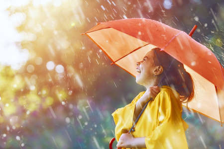 Happy funny child with red umbrella under the autumn shower. Girl is wearing yellow raincoat and enjoying rainfall. Kid playing on the nature outdoors. Family walk in the park.