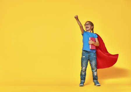 작은 아이 슈퍼 히어로 재생됩니다. 밝은 색 벽의 배경에 아이. 교육 및 성공 개념입니다. 노란색, 빨간색 및 파란색입니다.