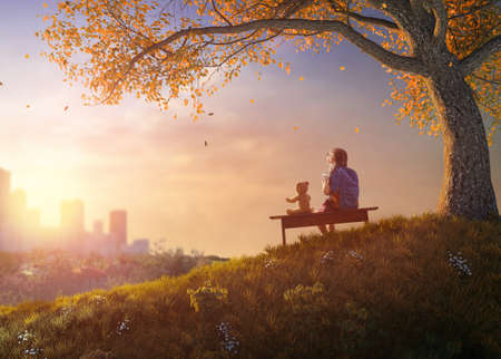 Back to school! Happy cute industrious child sitting on the bench near tree on background of sunset urban landscape. Concept of successful education. Standard-Bild