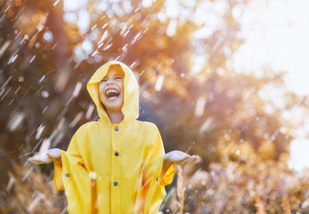 Happy funny child under the autumn shower. Girl is wearing yellow raincoat and enjoying rainfall.