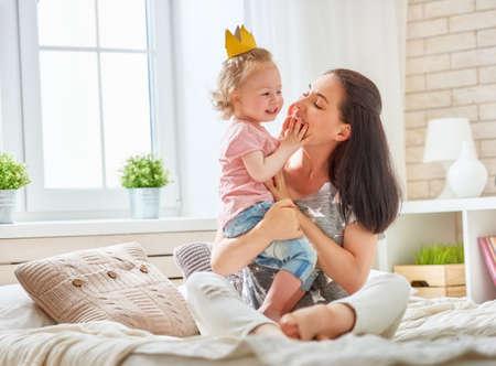 Gelukkige liefdevolle familie. Moeder en haar dochter kind baby meisje spelen en knuffelen op het bed in de slaapkamer.