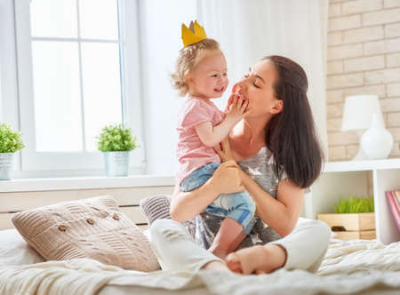 Happy loving family. Mother and her daughter child baby girl playing and hugging on the bed in bedroom. Stok Fotoğraf