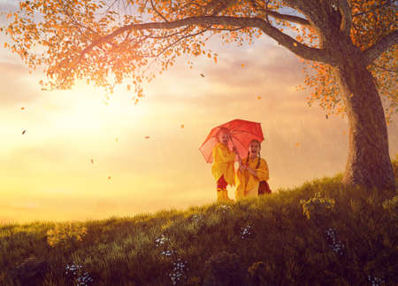 Two happy funny children under the autumn shower. Girls are wearing yellow raincoats and enjoying rainfall. Sisters playing together on the nature outdoors. Family walk in the park.