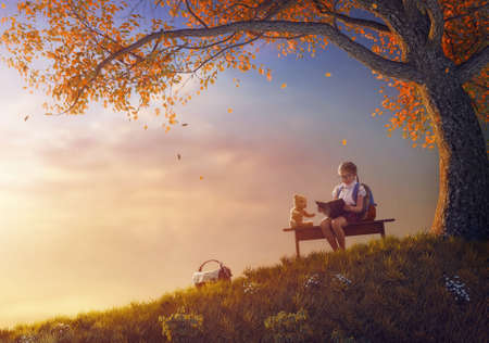 Back to school! Happy cute industrious child reading the book for her toy near tree on background of sunset. Concept of successful education and reading.