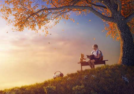 Retour à l'école! Heureux enfant laborieux, lisant le livre pour son jouet près de l'arbre au fond du coucher du soleil. Concept d'éducation et de lecture réussies. Banque d'images - 83953134